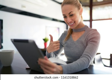 Young caucasian woman talking in video chat with her friend via digital tablet while sitting in coffee shop. Positive female freelancer choosing application on tablet while sitting in cofffee shop.