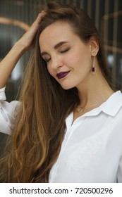 Young caucasian woman touches her hair with a dreamy expression on her face