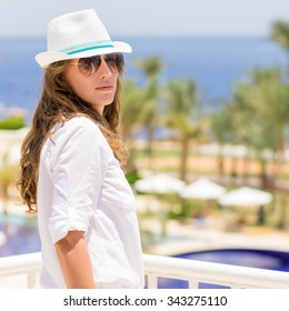 Young caucasian woman in the tropical resort hotel. Beautiful girl in white hat and shirt with copy space on summer vacation background