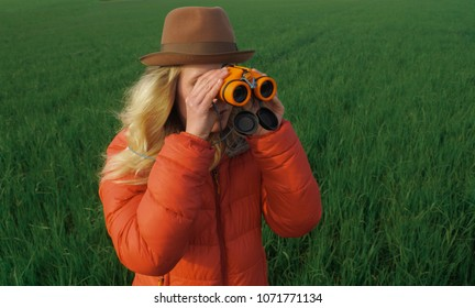 young caucasian woman using binoculars outdoors