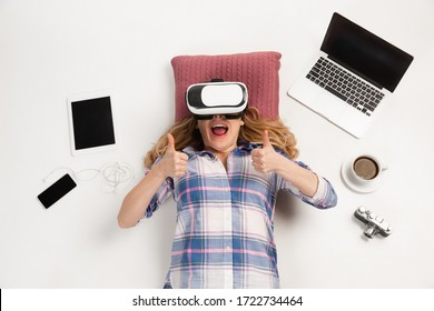 Young caucasian woman using devices, gadgets isolated on white studio background. Concept of modern technologies, gadgets, tech, emotions, ad. Copyspace. Gaming, shopping, meeting online education.