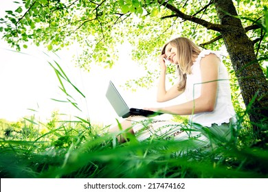 Young Caucasian woman using Laptop on nature, sitting in the grass in the park.