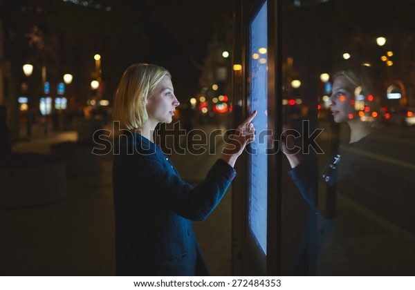 Young caucasian woman using a touch sensitive display while standing on the street with night lights on background, female touching futuristic smart bus station display for self service information