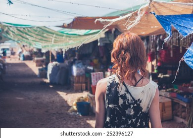 A young caucasian woman is walking around a small town in a developing country