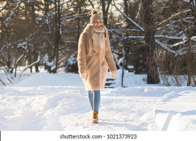 Young caucasian woman walking on snow path in park at sunny frosty day, enjoying winter moments and nature, wearing winter clothes - beige coat, scarf, hat with pompon/ Winter time, walking - concept