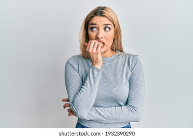 Young caucasian woman wearing casual clothes looking stressed and nervous with hands on mouth biting nails. anxiety problem.