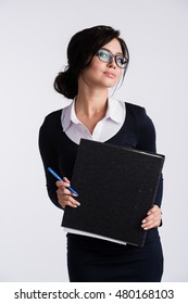 Young Caucasian woman wearing dark blue dress, white shirt, holding a ring binder folder and pen. Isolated on light background.