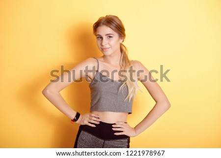 3b39d9fb0e Young caucasian woman wearing in sports bra over isolated background  smiling with hands on hips with