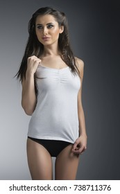 Young caucasian woman wearing white camisole lingerie in studio lighting
