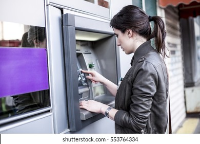 Young Caucasian woman withdrawing money from an ATM.