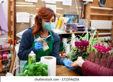Junge Kaukasierin bei der Arbeit in einer Kindergarten. Der Florist trägt eine Maske und Handschuhe, um eine Infektion des Coronavirus covid-19 zu vermeiden. Das Foto zeigt einen Kunden, der mit Euro-Münzen und -Banknoten bezahlt.