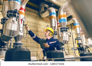 Young Caucasian worker in protective suit tightening the valve and using tablet while standing in heating plant.