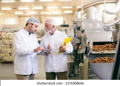 Young Caucasian worker showing to his older colleague statistic on tablet while standing in food factory.