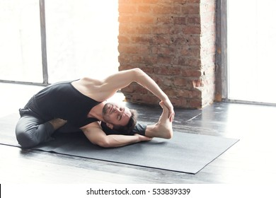 Young caucasian yoga man practicing yoga near a picture window with red brick wall. Yogi man workout, sitting in asana and meditates on urban background indoors