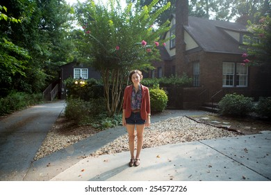 young caucasion woman standing in front of tudor home