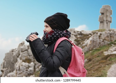 young caucassian woman looking through binoculars at the magnificent landscape at the Pen Hir cape in France.