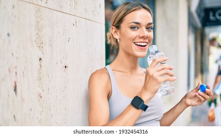 Young cauciasian fitness woman wearing sport clothes training outdoors drinking fresh water
