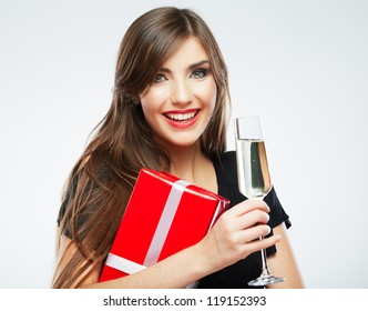 Young celebrating woman black dress . Beautiful model portrait isolated over studio background hold wine glass and christmass gift