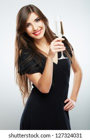Young celebrating woman black dress . Beautiful model portrait isolated over studio background hold wine glass.