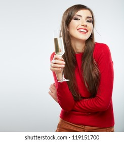 Young celebrating woman in red. Beautiful model portrait isolated over studio background hold wine glass.