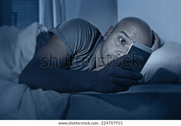 young cell phone addict man awake at night in bed using smartphone for chatting, flirting and sending text message in internet addiction and mobile abuse concept