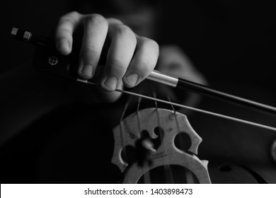 A young cellist practices intensely on his cello, viewed from the bridge and bow side