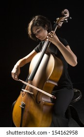 Young cellist silhouetted against black