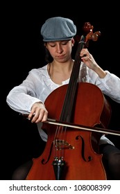 Young cellist sitting and playing cello on black background