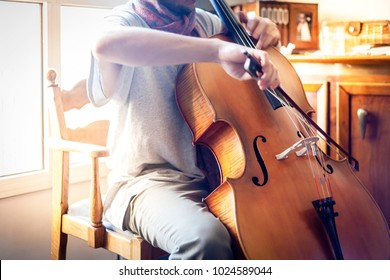 young cello player with scarf faceless shot making music with a violoncello sitting on a wooden chair. Musician rehearsing at home.