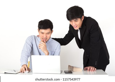 A young CEO touch shoulder his colleague and supporting his engineer for new project. Business mans working and chatting in office. Coworker looking in laptop. Business concept in front view.