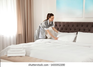 Young chambermaid making bed in hotel room. Space for text
