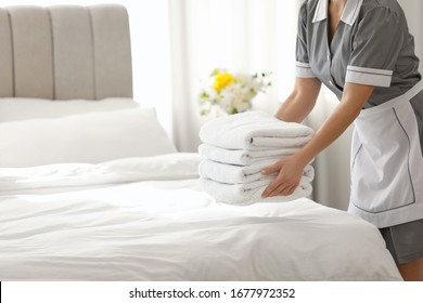 Young chambermaid putting stack of fresh towels in bedroom, closeup. Space for text