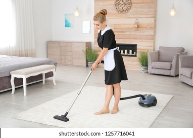 Young chambermaid removing dirt from carpet with vacuum cleaner in hotel room