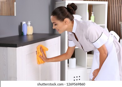 Young chambermaid wiping dust from furniture with rag in bathroom