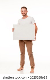 A young charismatic man with a white sign in his hands. You can use it to advertise, place a logo. He is dressed in brown pants, a white t-shirt, barefoot. Full length of the photo, different emotion
