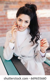 Young charismatic woman with dark wavy pony tail having red manicure dressed eleganltly talking on her mobile phone with smile while sitting at cafe waiting for her order. Communication concept