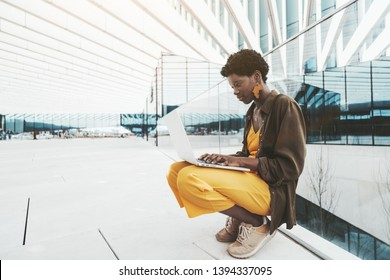 Young charming African female undergraduate in yellow overalls is using her laptop in an outdoor area with stripes on the top; a fancy black student girl with a netbook is leaning against glass fence