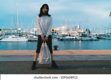 Young charming asian traveler female standing at the city b erth with the backpack in her hands at the evening. International student girl enjoying evening walk at the river side of the city.