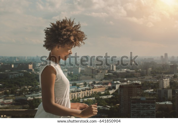 Young charming black Brazilian teen girl with beautiful curly afro hair in white dress standing on observation point very high and smiling, sunny summer cityscape below in blurred background