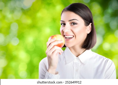 Young charming brunette woman biting apple with green nature background.Woman in white shirt eating apple,business woman eating healthy snack.Corporate woman on break eating healthy and organic