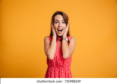 Young charming brunette woman with happy exited emotional face, holding her head with hands, looking at camera, isolated over yellow background