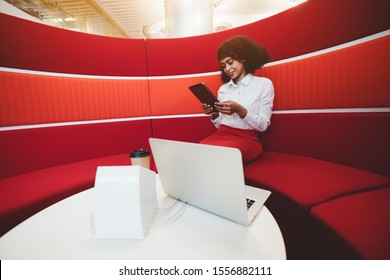 A young charming cheerful African-American business lady is sitting in a cozy office lounge zone on a curved red sofa and using her tablet pc, a laptop and a dock station on the table in front of her