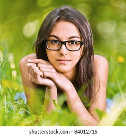 Young charming dark-haired woman in glasses with black frame lies on green grass in summer city park.
