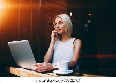 Young charming female freelancer calling with mobile phone while sitting in cafe at the table with net-book, blonde Caucasian woman talking on cell telephone during work on portable laptop computer