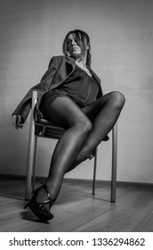 Young charming girl sitting on a chair in a jacket, pantyhose and shoes with heels