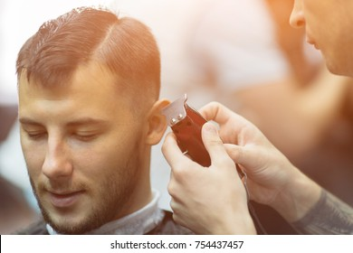 young charming man in barbershop salon while shearing with clipper by hairdresser, sunlight