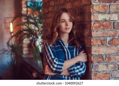 A young charming sensual girl stands leaning against a brick wal