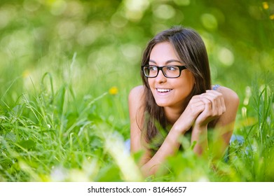 Young charming smiling dark-haired woman in glasses with black frame lies on green grass in summer city park.