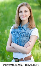 Young charming smiling woman in a denim jacket on the background of a summer green city park.
