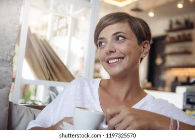 Young charming woman with beautiful smile enjoying coffee break